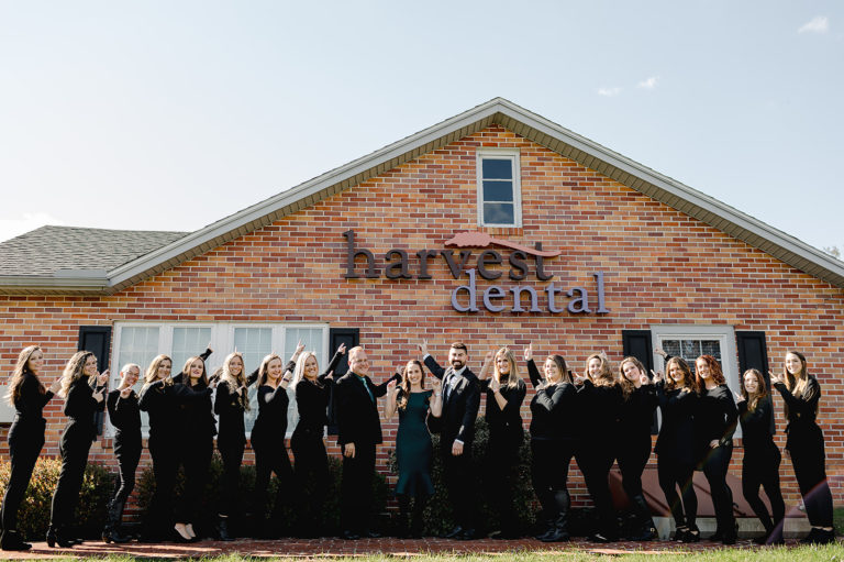 the whole harvest dental team standing in front of dental practice pointing up at sign